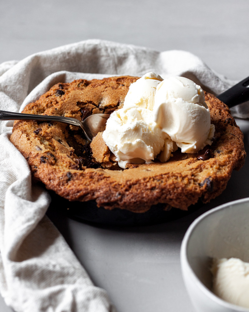 A stuffed chocolate chip skillet cookie topped with ice cream