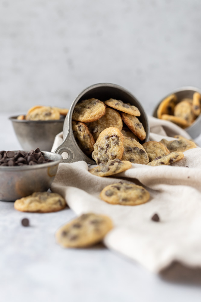 A small cup of mini chocolate chip cookies tipped over