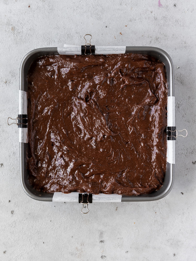 The brownie batter poured over the cookie dough in the prepared pan