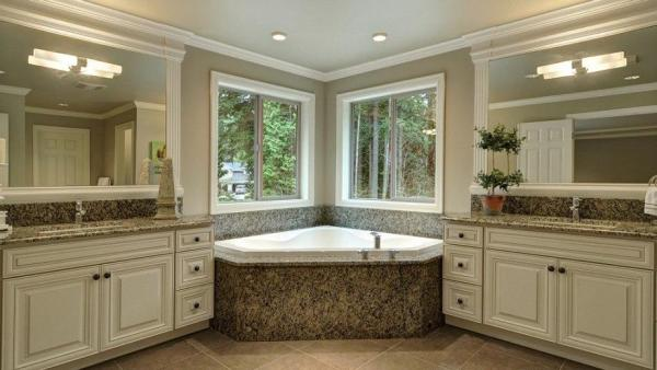 Custom built bathroom with his and her vanities and extra large tub