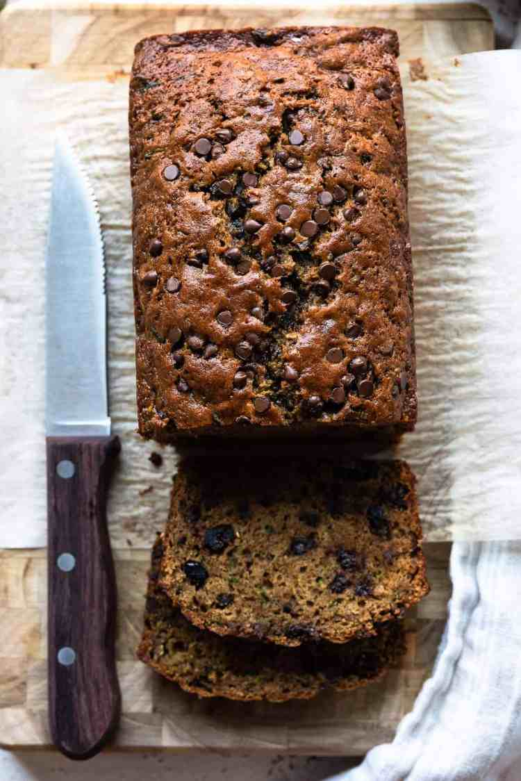 Zucchini bread with dried cranberries and chocolate chips sliced on a cutting board.