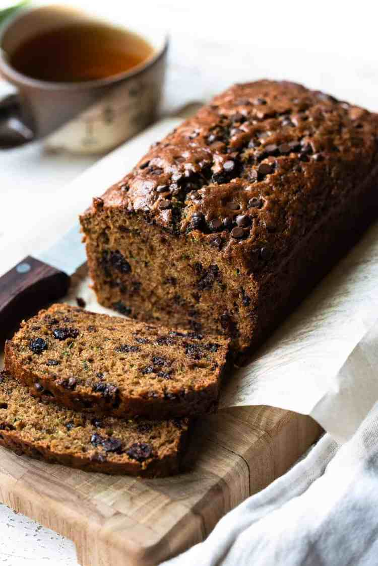 Zucchini bread with cranberries and chocolate chips sliced on a cutting board with a cup of tea in the background.
