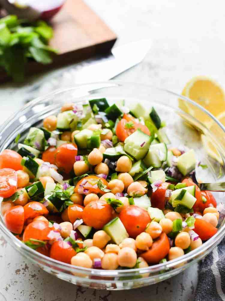 chick pea salad with tomatoes and cucumbers in a glass bowl on a rustic white background