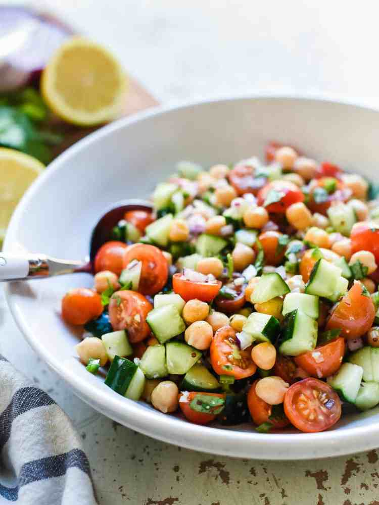 Chickpea salad with garbanzo beans, cherry tomatoes, cucumbers, red onions, cilantro, and a delicious dressing in a white bowl.