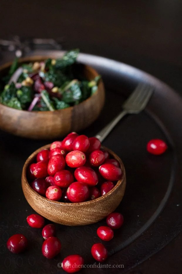 Fresh cranberries in a wooden bowl for Cranberry Walnut Kale Salad with Fresh Cranberry Vinaigrette