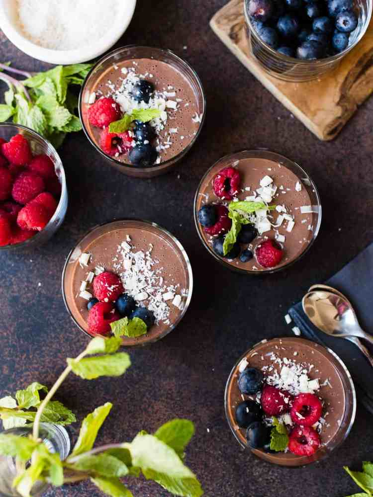 Glasses of Cheat's Chocolate Hazelnut Mousse with berries, coconut and white chocolate. An easy recipe for tofu chocolate mousse.