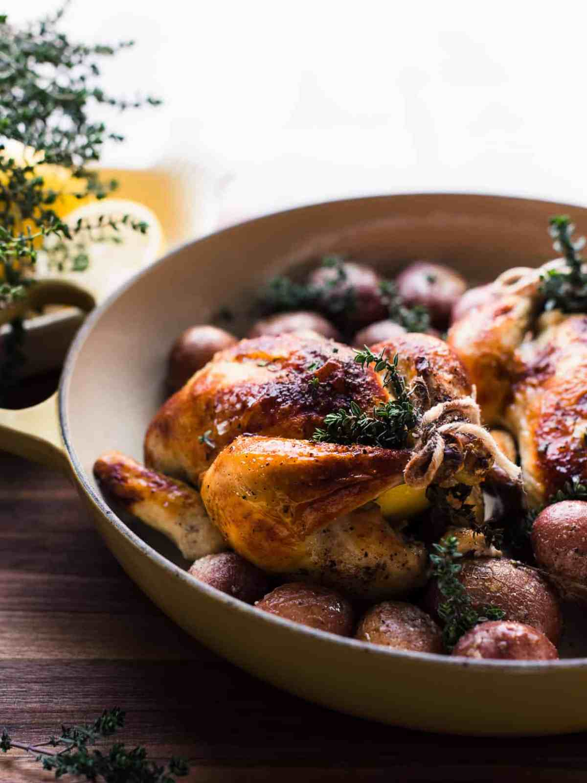 Roasted Buttermilk Brined Cornish Hens with sprigs of thyme on a bed of red potatoes.