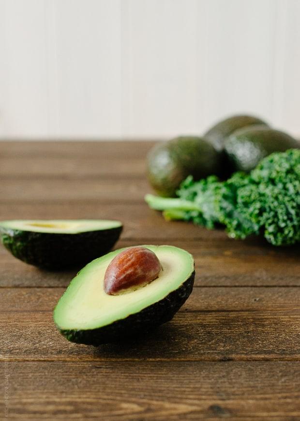 Avocado Kale Superfood Smoothie ingredients: avocado cut in half and kale leaves