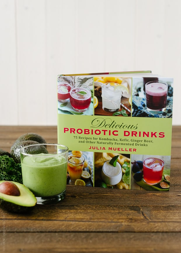 Green Avocado Kale Superfood Smoothie in a glass next to an avocado, kale leaves, and a copy of the Delicious Probiotic Drinks cookbook