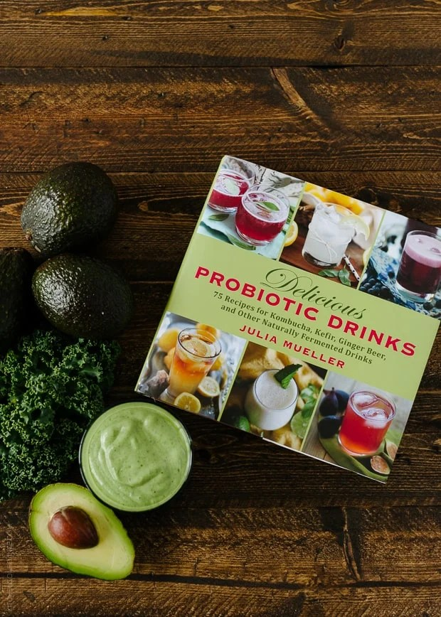 Delicious Probiotic Drinks cookbook on a wooden background with Avocado Kale Superfood Smoothie, avocados, and kale