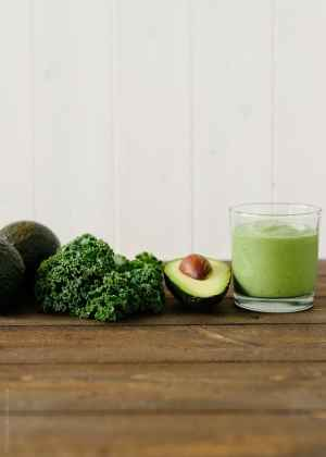 Green Avocado Kale Superfood Smoothie in a tall glass next to an avocado and kale leaves