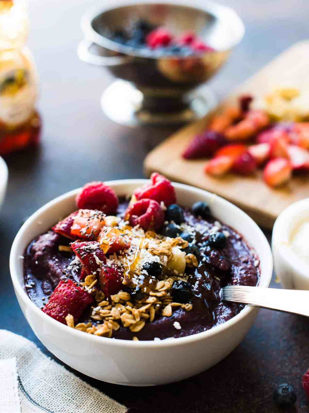 Acai Berry Bowl topped with strawberries, blueberries, raspberries, bananas, coconut, granola, chia seeds and honey.