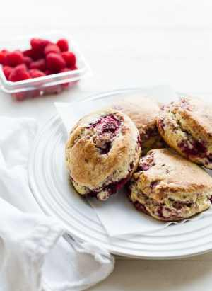 coconut raspberry scones on a white plate, raspberries in the background