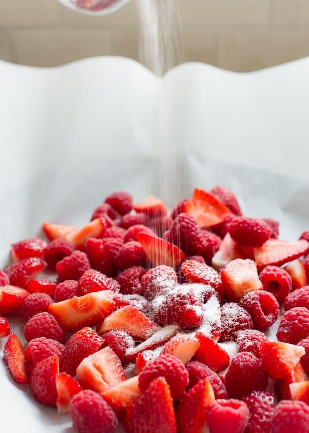 Sprinkling fresh strawberries and raspberries with sugar.
