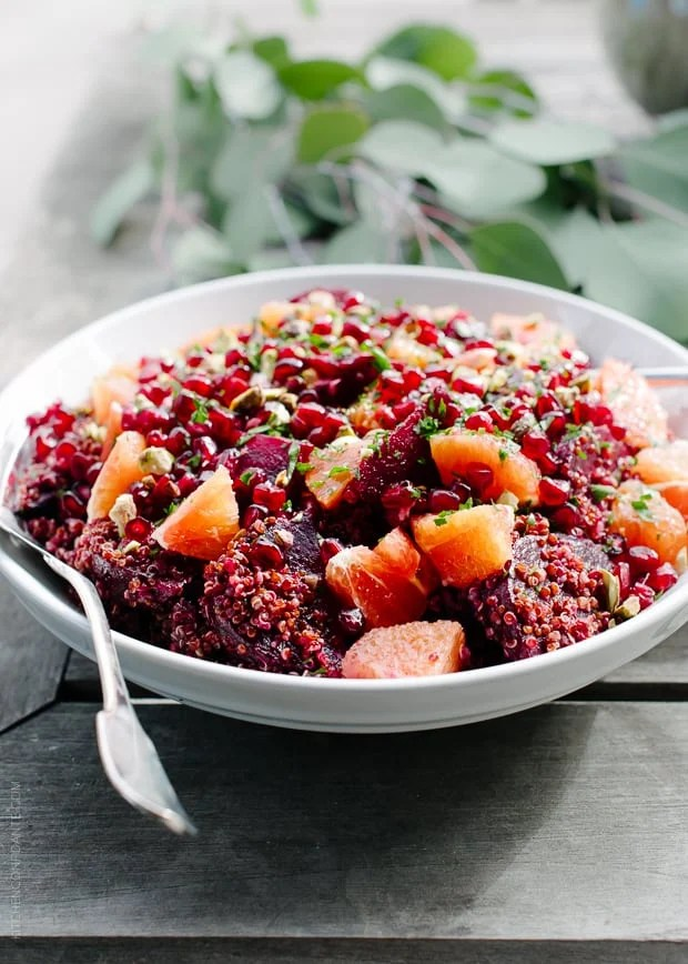 Quinoa Salad with Roasted Red Beets, Oranges and Pomegranate in a white bowl.