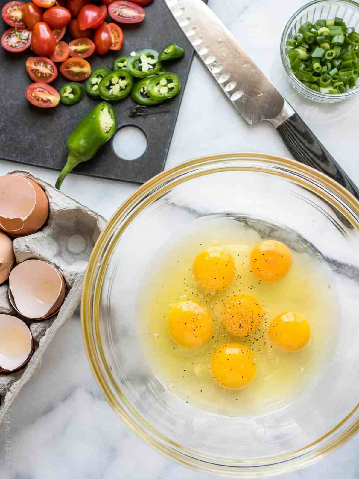 Six eggs cracked into a glass bowl surrounded by chopped peppers and tomatoes.