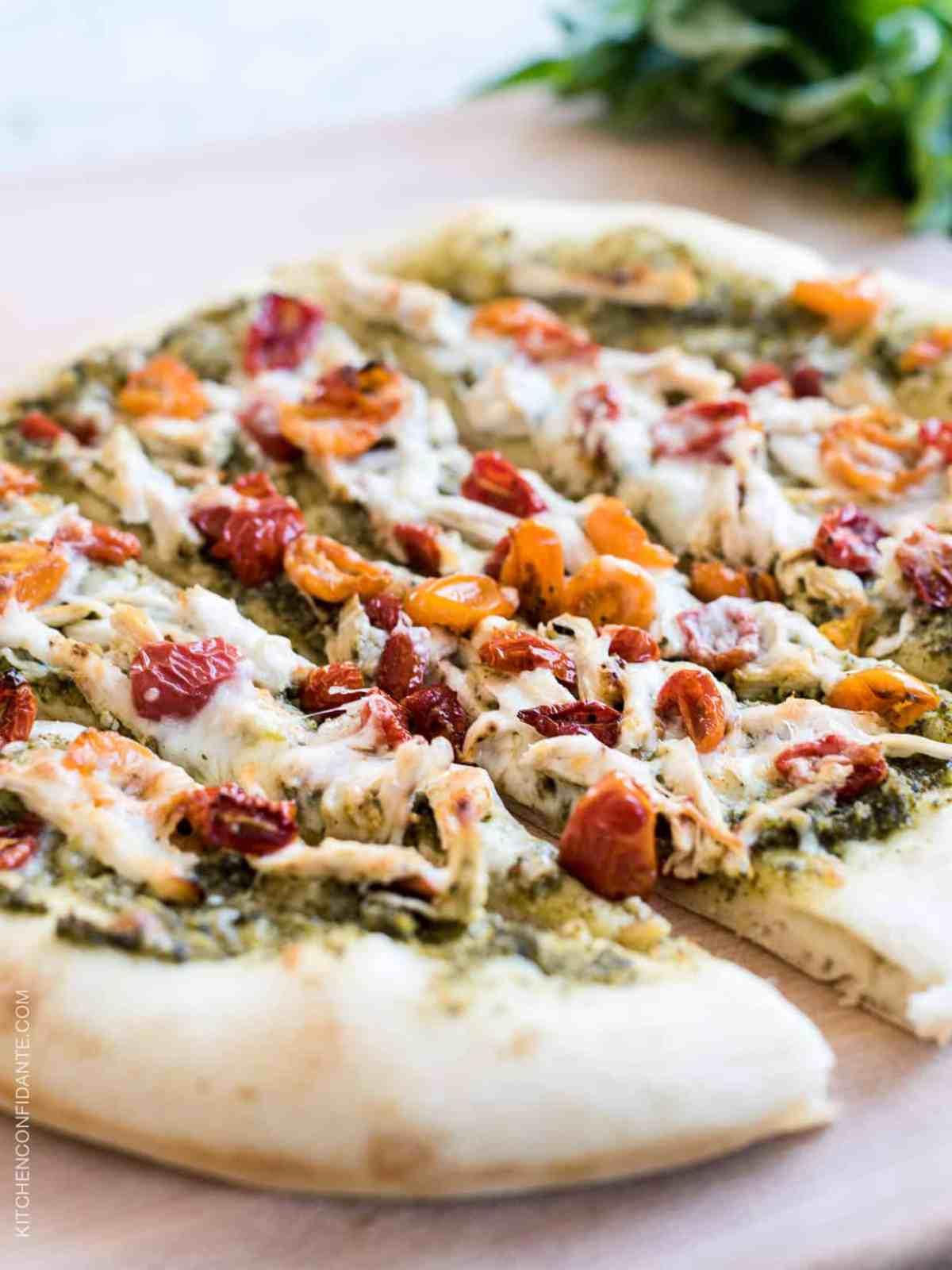 Chicken Pesto Pizza sliced on a wood board.