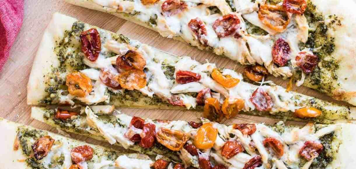 Chicken Pesto Pizza sliced on a cutting board.