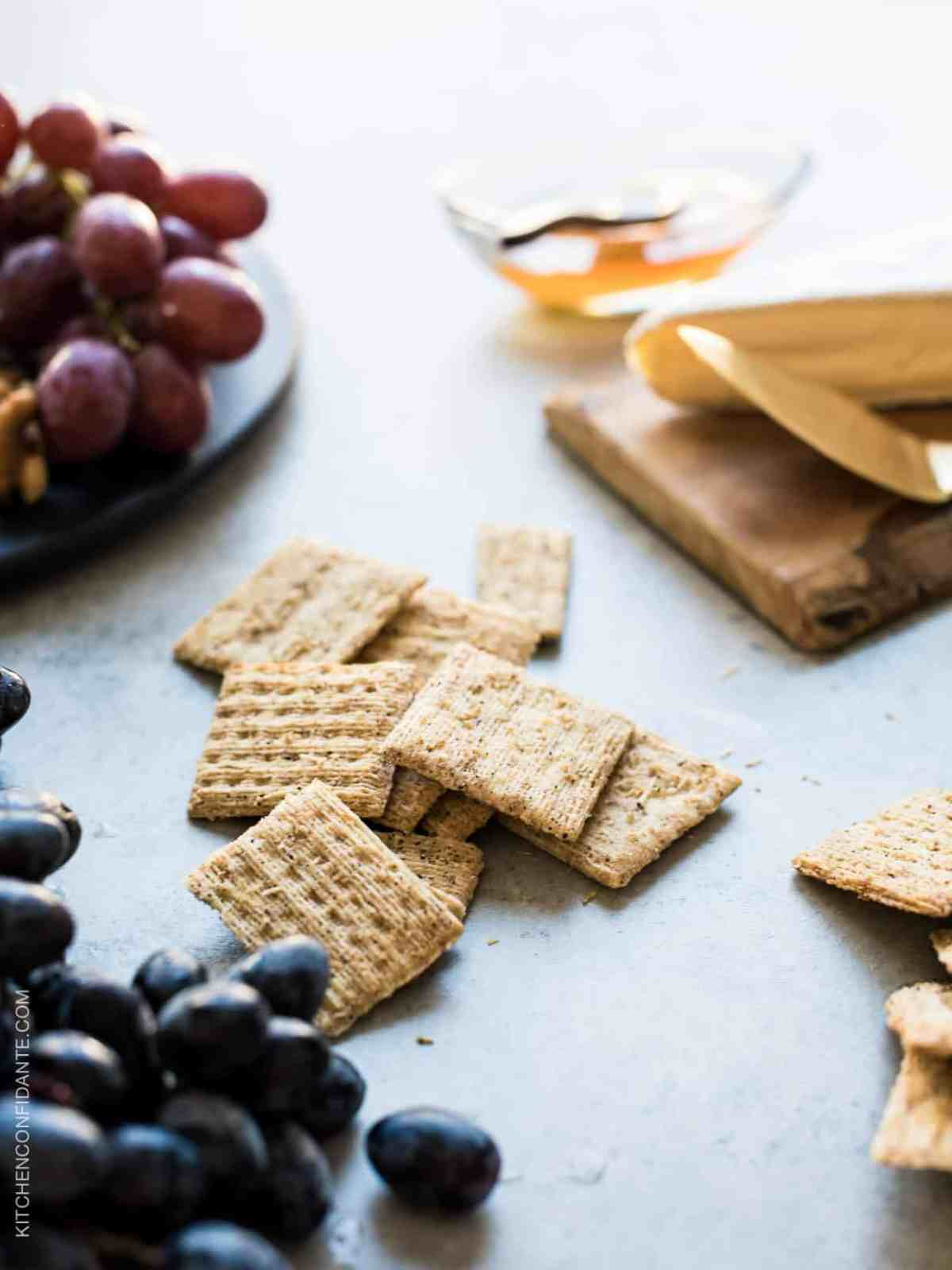 Triscuit crackers and grapes on a rustic surface.