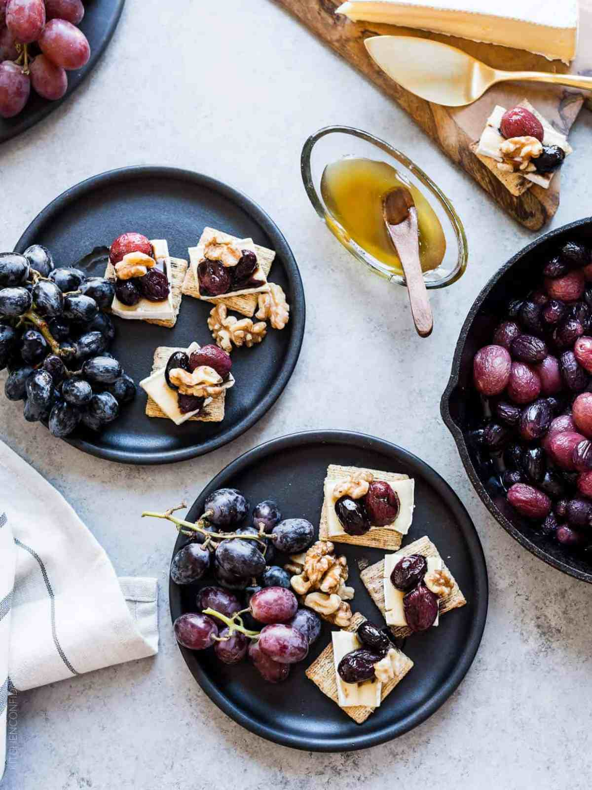 Caramelized Grape, Brie and Walnut Bites made with TRISCUIT crackers and served on dark plates with bunches of grapes.