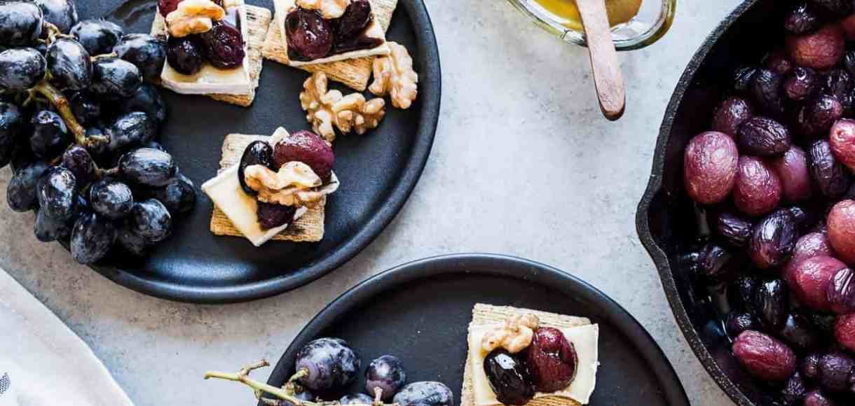 Caramelized Grape, Brie and Walnut Bites made with TRISCUIT crackers and served on dark plates.