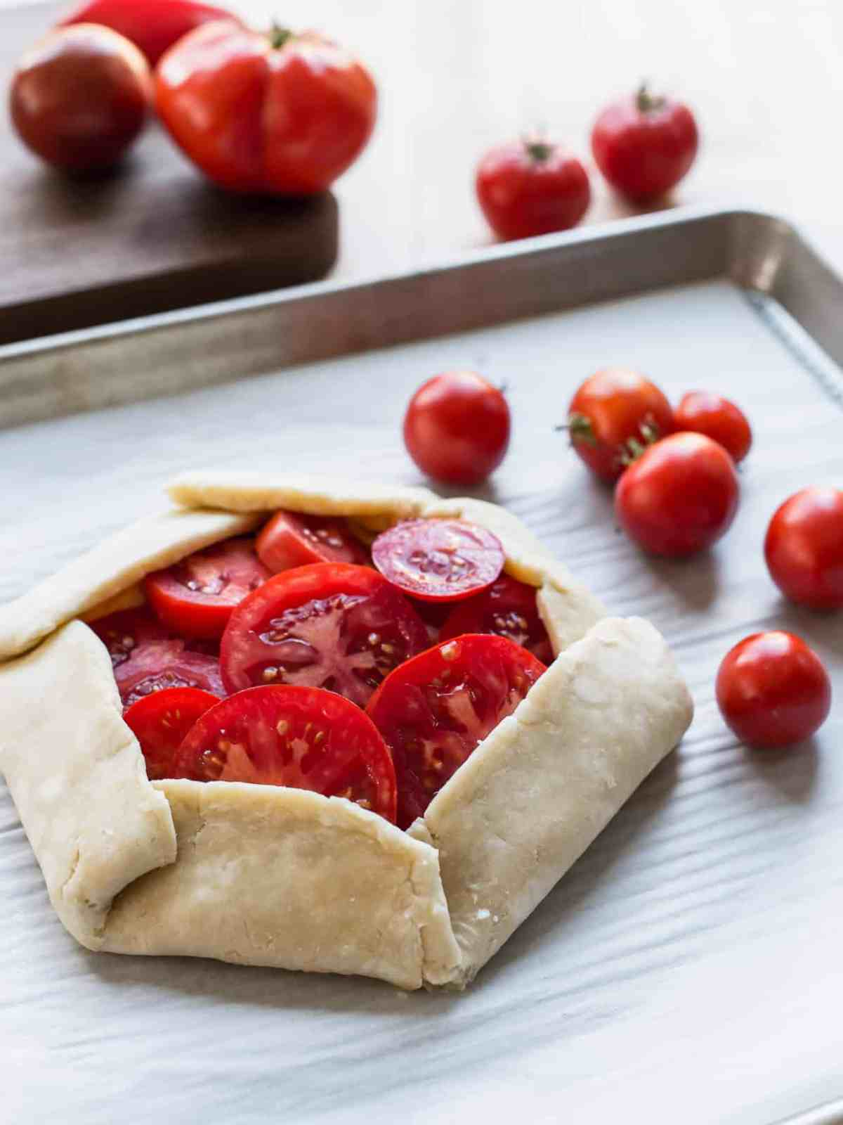 Tomato Ricotta Galette - this rustic pie recipe marries the flavors of a pizza with a flakey crust and juicy heirloom tomatoes.