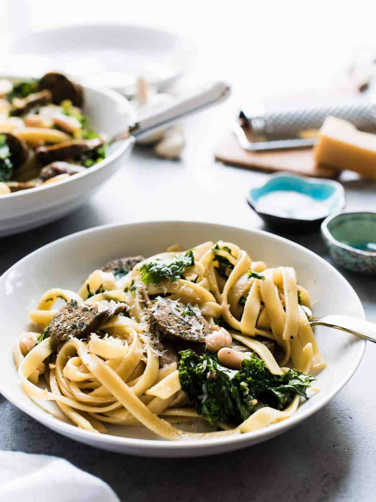 Fettuccine with Chicken Sausage, Kale and Cannellini Beans in a white bowl with the pasta twirled around a fork.