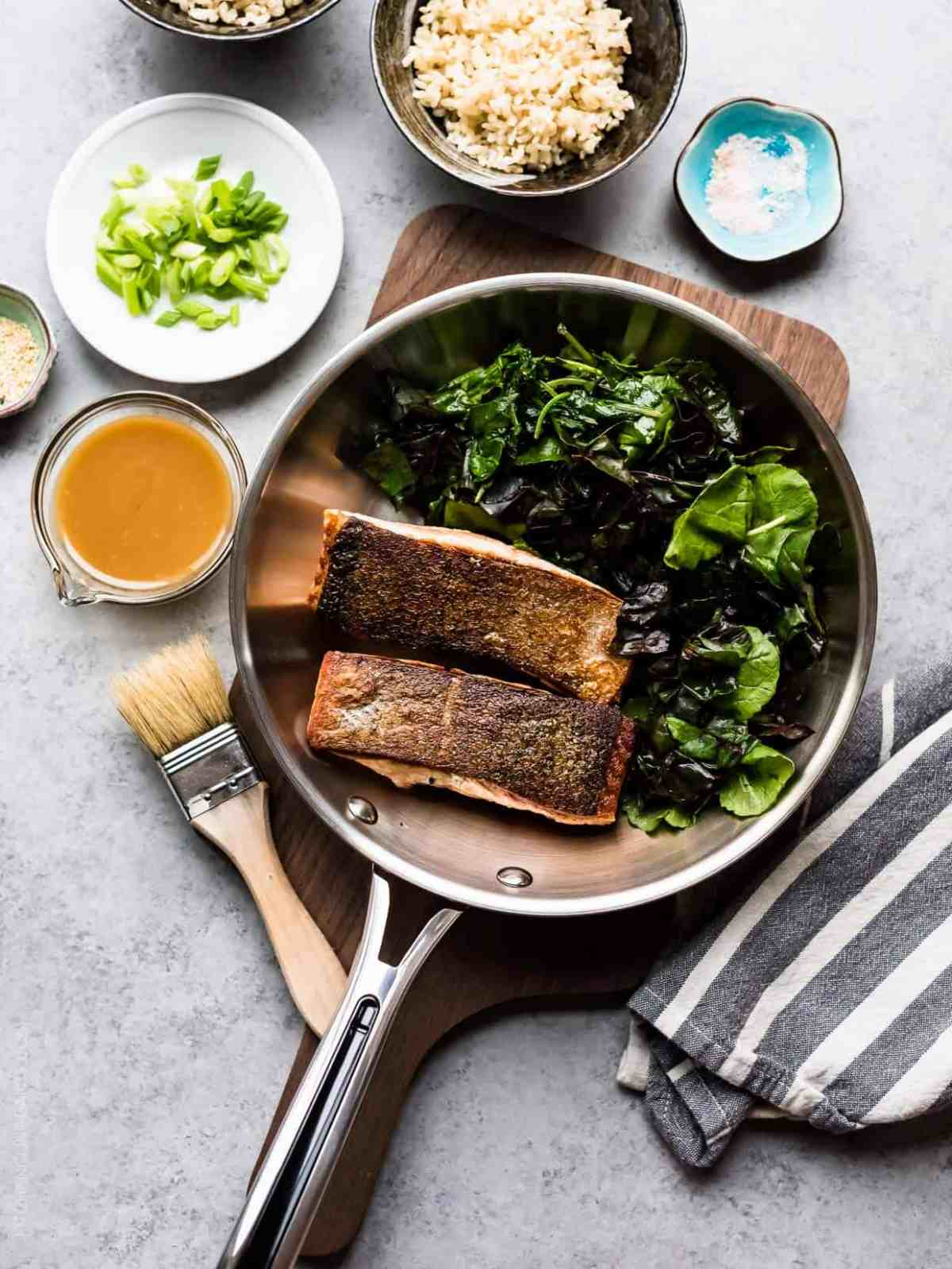Miso Maple Glazed Salmon in Revere Cookware surrounded by a wilted green salad and additional ingredients.