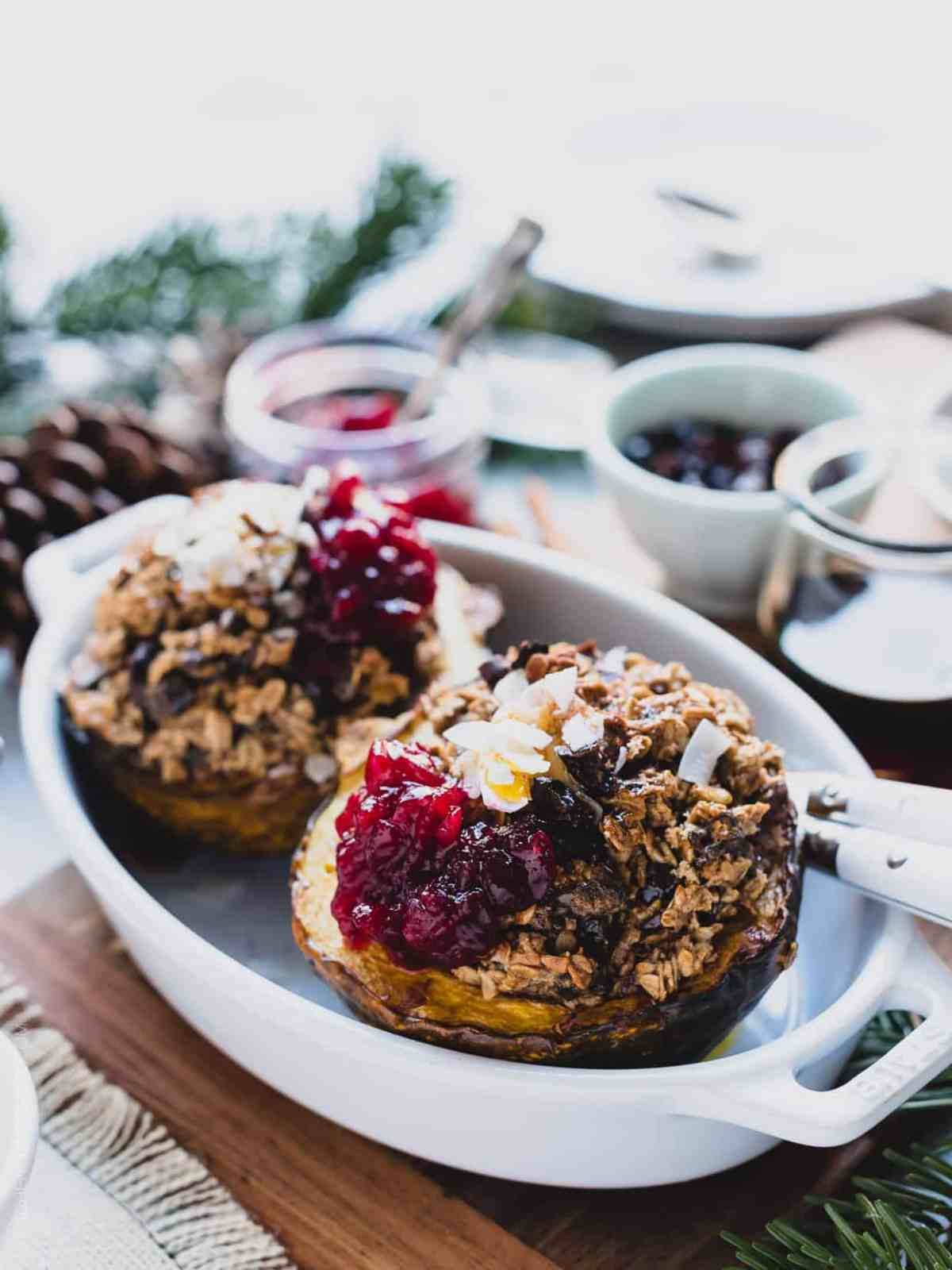 Two halves of Baked Oatmeal Stuffed Acorn Squash in a white baking dish garnished with cranberry sauce.