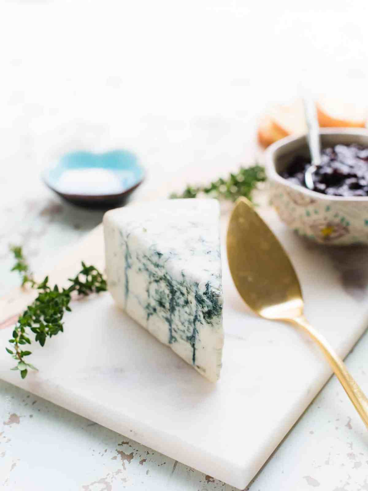 Wedge of Gorgonzola cheese on a white serving board ready to be used to prepare Crostini with Gorgonzola and Prune Chutney.