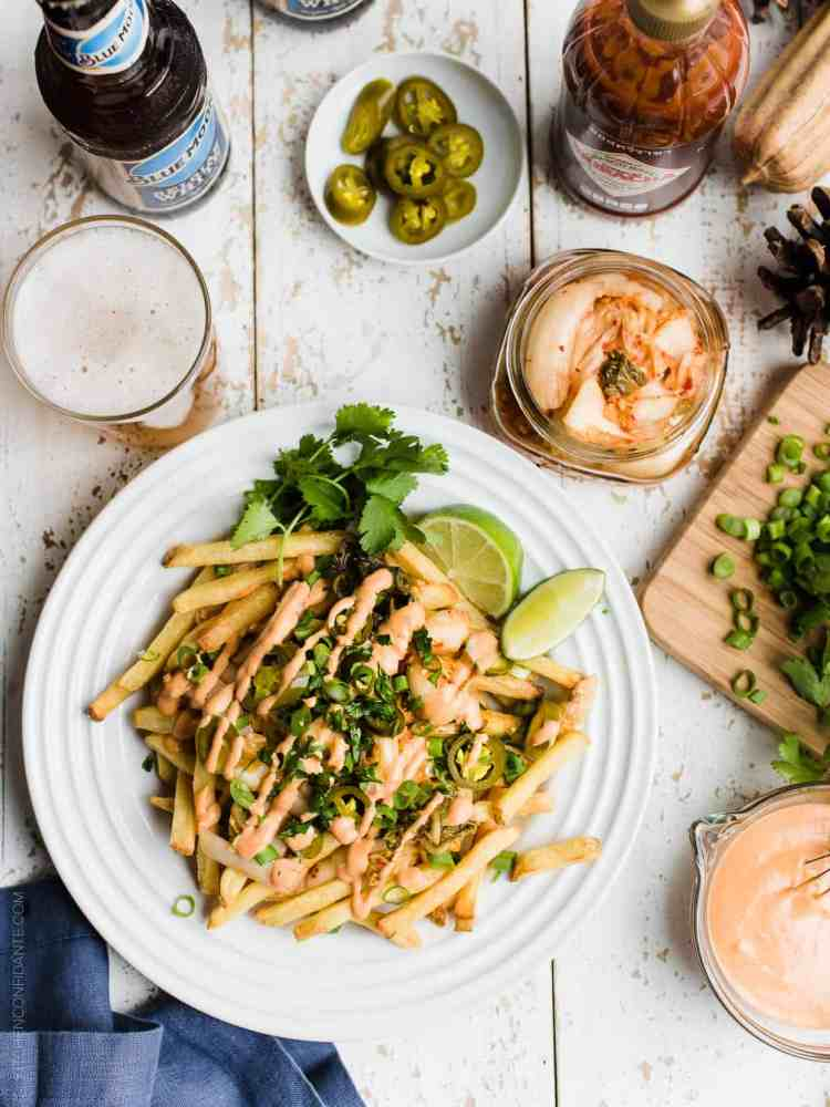 White plate of French fries topped with kimchi, pickled jalapenos, cilantro, green onions, and Sriracha mayonnaise.