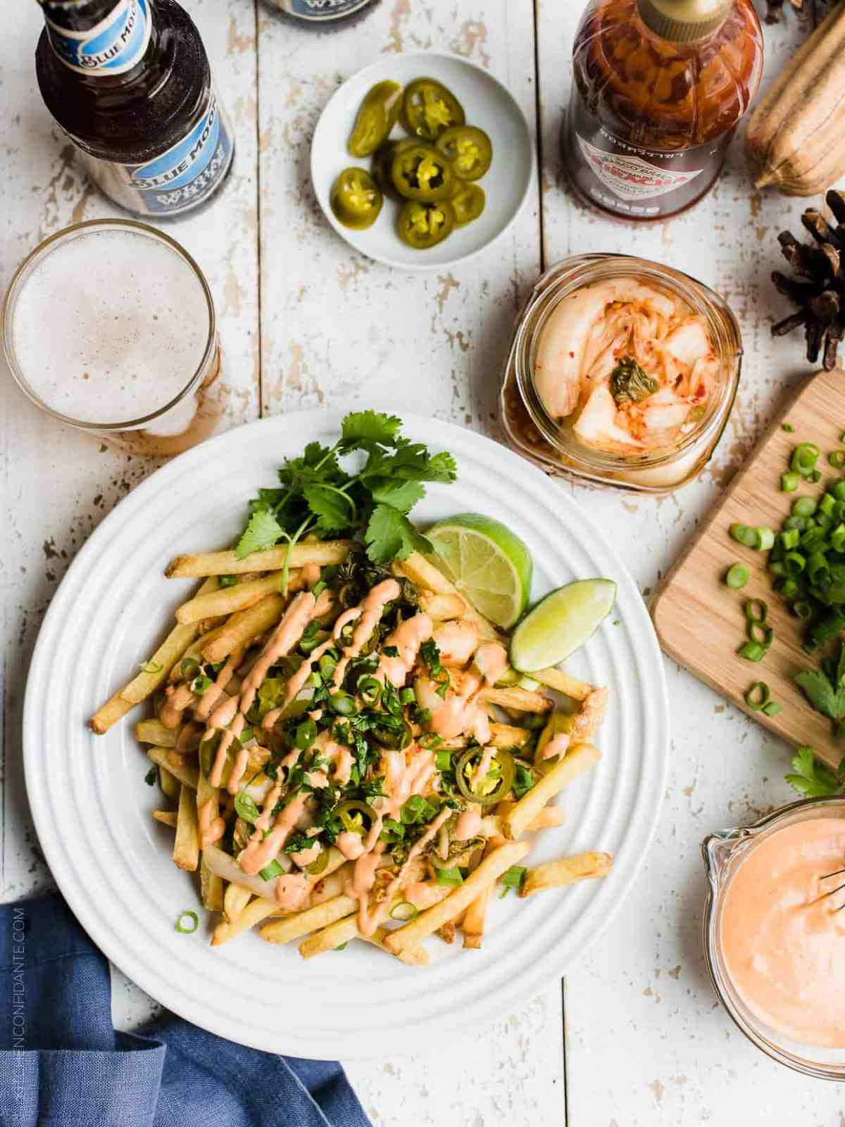 Overhead view of a plate filled with Kimchi French Fries and Belgian beer and a jar of kimchi in the background.