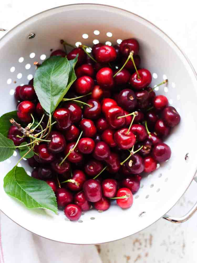 Fresh cherries in a white colander to make Homemade Cherry Pop Tarts