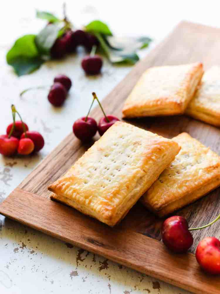 Homemade Cherry Pop Tarts without glaze on a wooden board with fresh cherries.