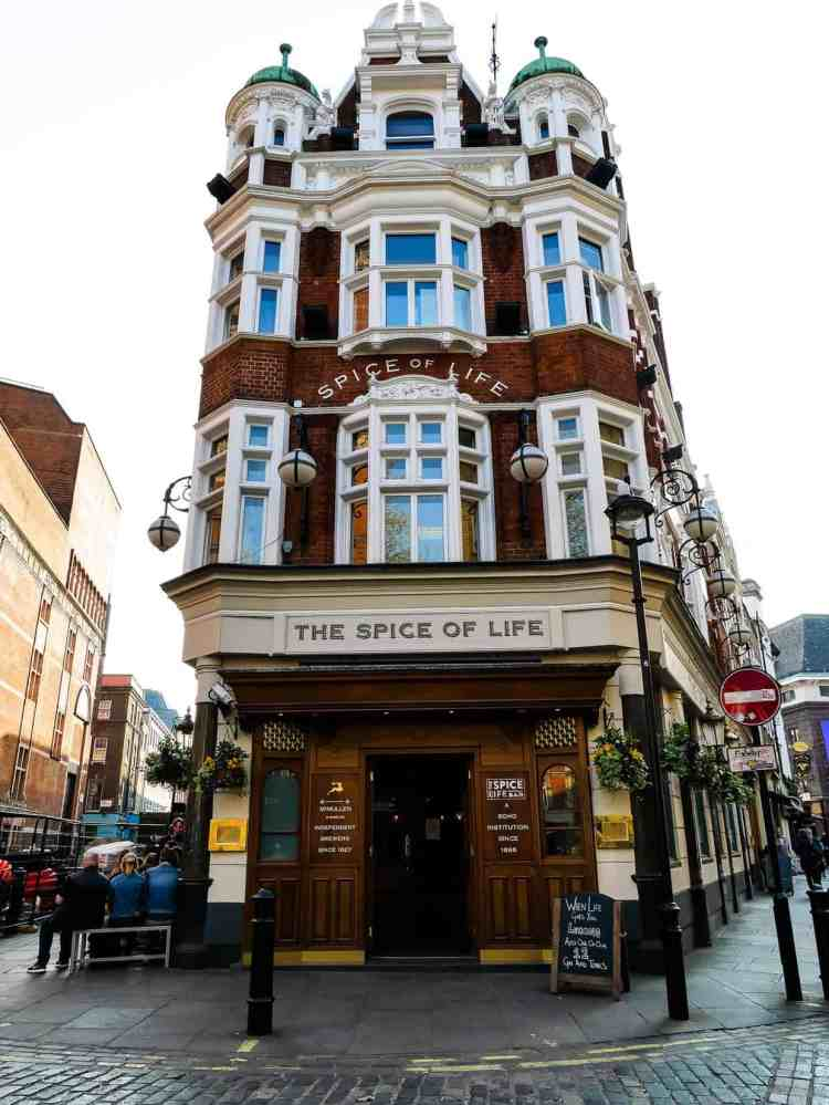 A tall, narrow brick building in London with lots of white windows. Sign says The Spice of Life.