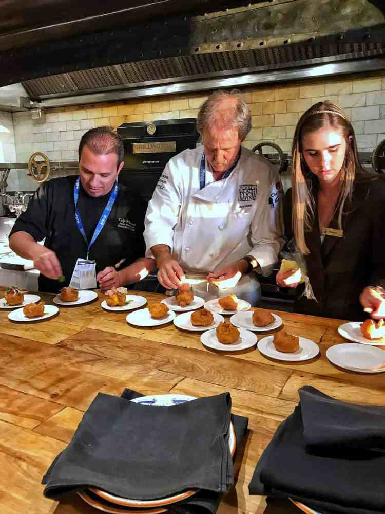 Two men and one woman arranging food on small plates in a professional kitchen at the Pebble Beach Food & Wine.