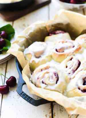 Cherry rolls with icing in a parchment lined cast iron pan.