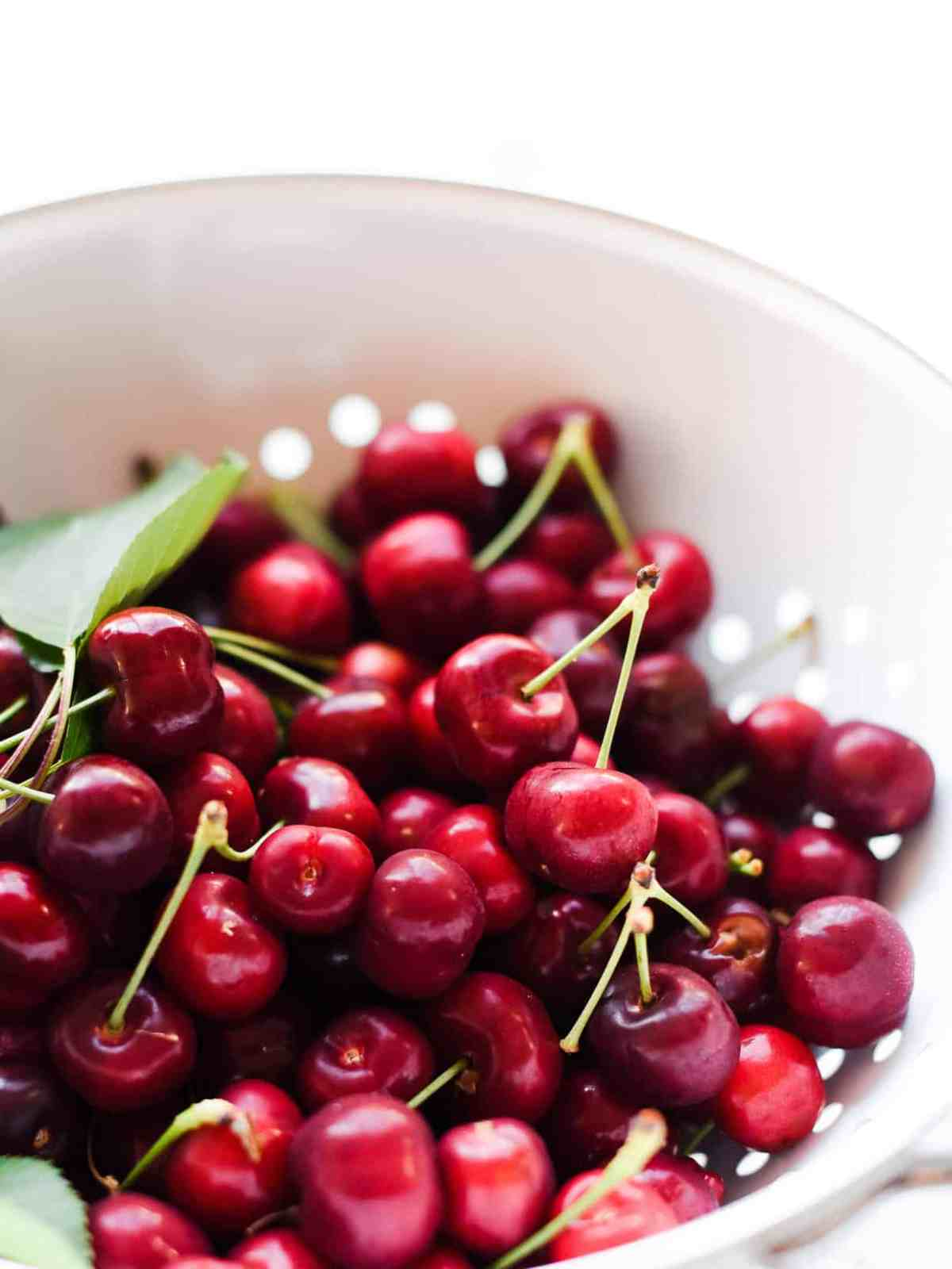 Fresh cherries with stems in a white colander.
