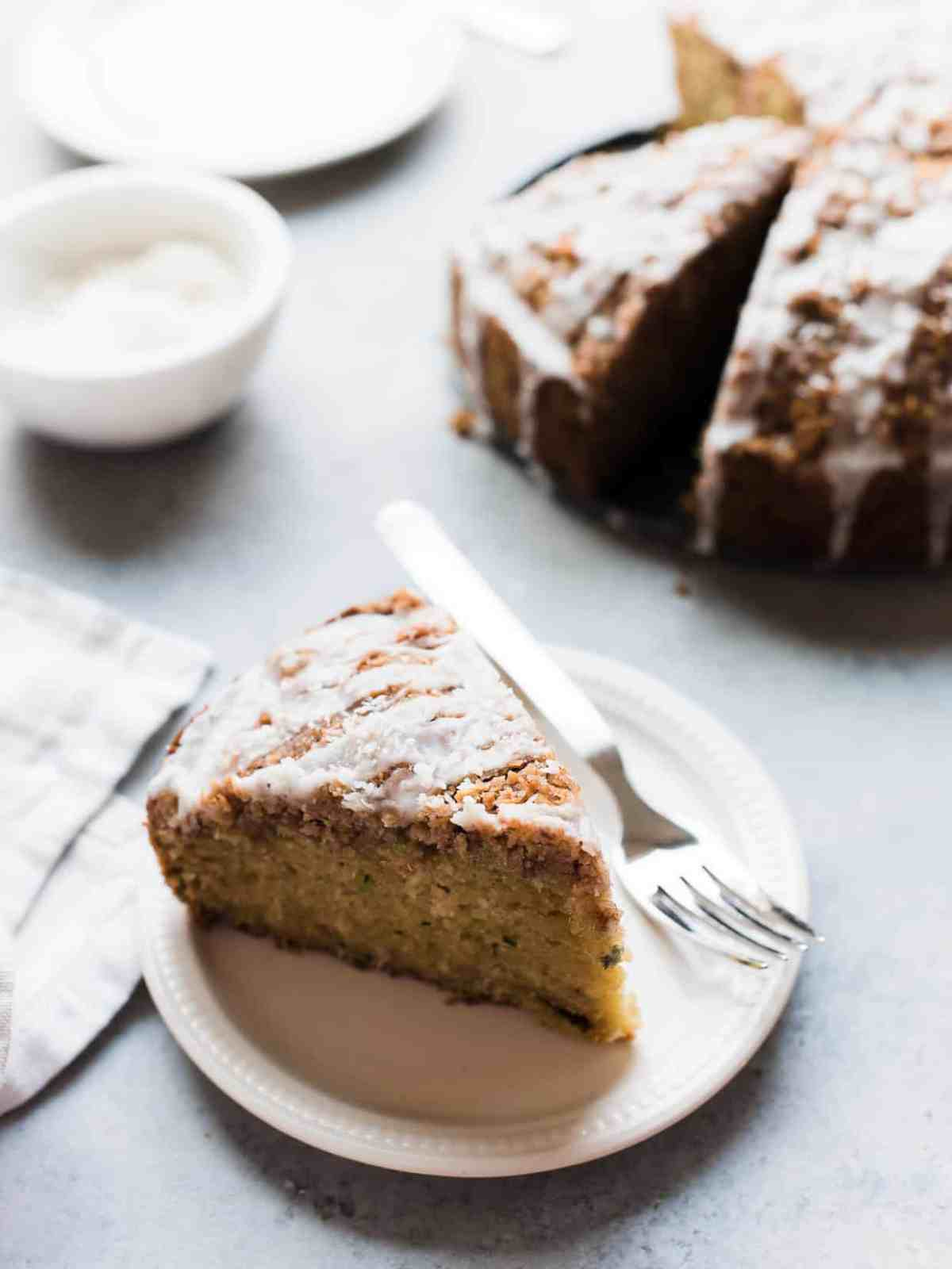 A slice of coconut zucchini coffee cake on a white plate.