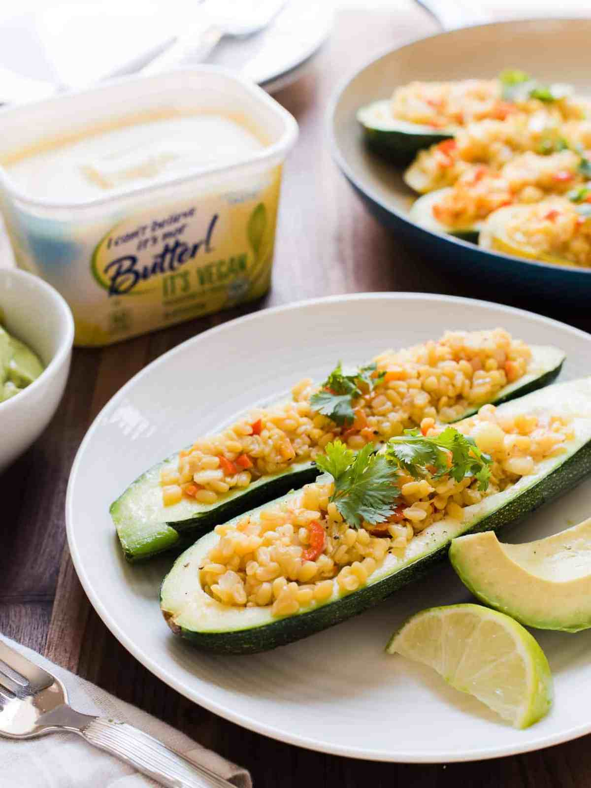 Stuffed yellow squash and zucchini with a tasty lentil filling served on a white plate.