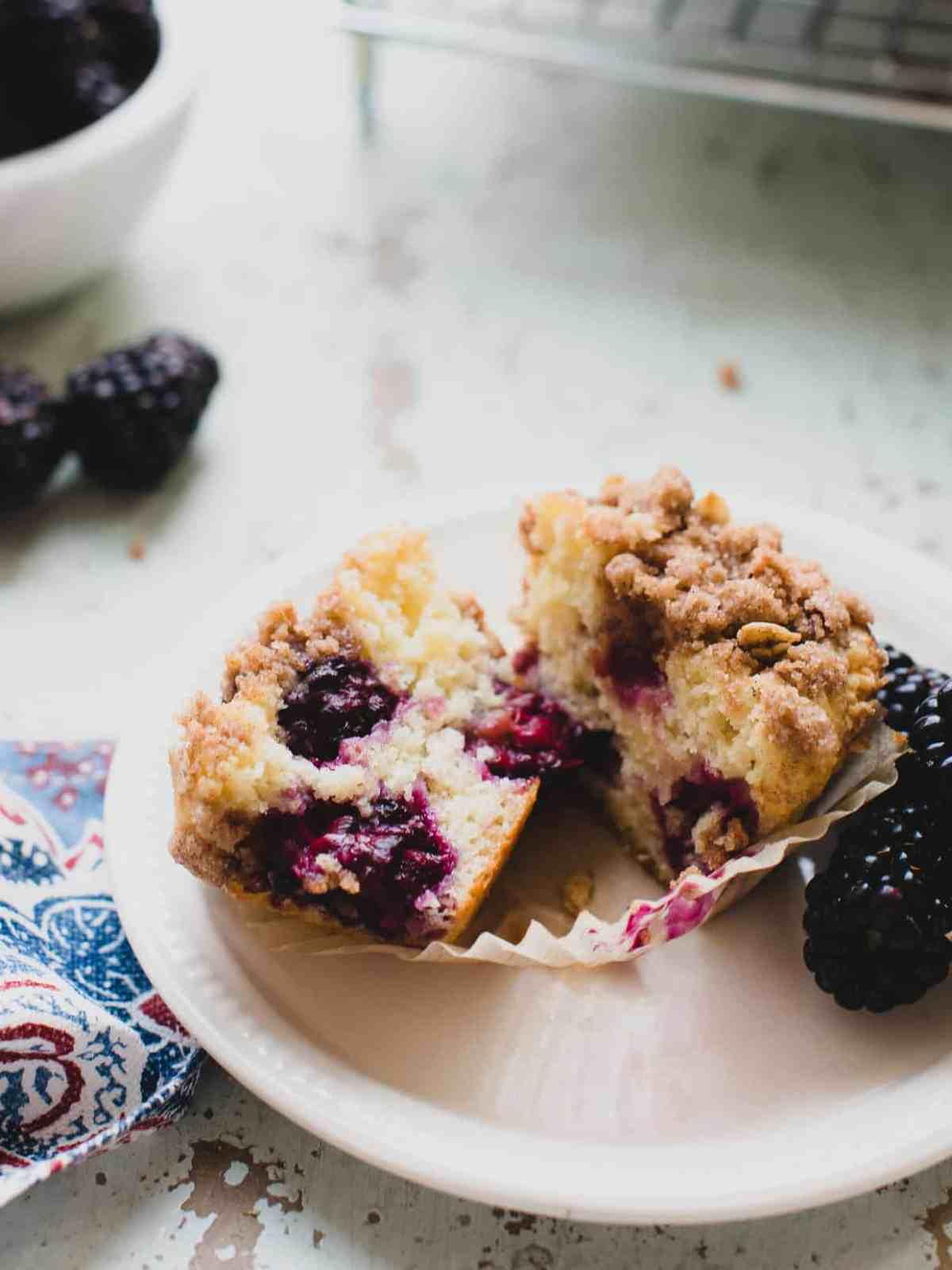 Freshly baked blackberry yogurt muffin cut in half on a white plate.