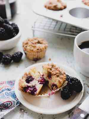 blackberry yogurt muffins cut in half on plate