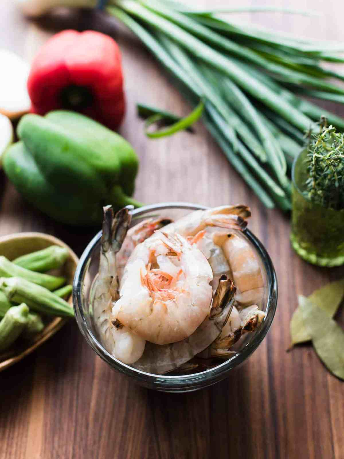Fresh shrimp surrounded by bell peppers and other ingredients on a wooden surface.