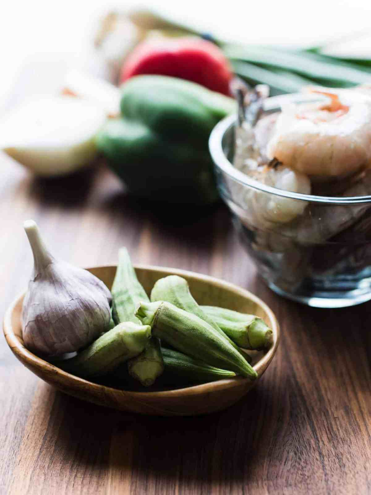 Bowl of okra and garlic on a wooden surface.