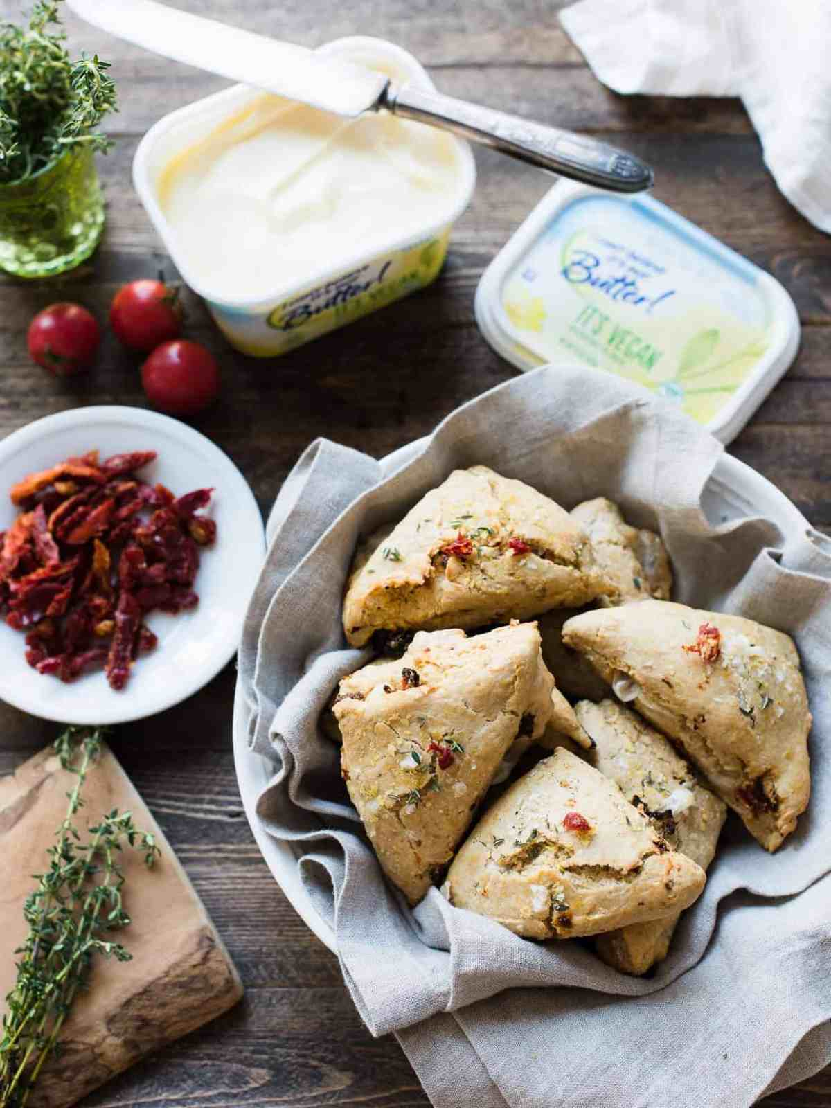 Freshly baked Sun-dried Tomato and Thyme Scones surrounded by sun-dried tomatoes, thyme, and other ingredients.