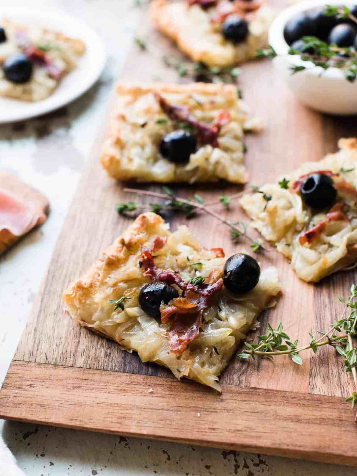 Slices of Pissaladière with Prosciutto on a wooden serving board.