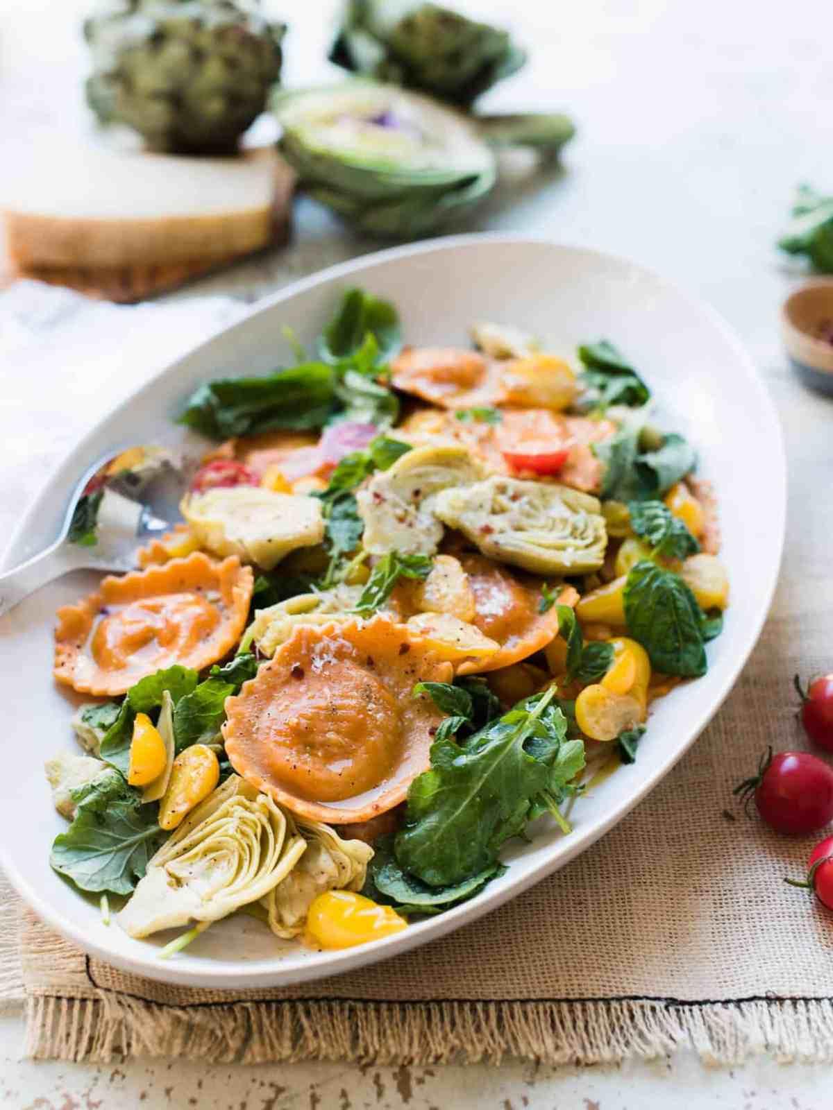 Platter of Tomato and Mozzarella Ravioli with fresh tomatoes, baby kale and artichokes.