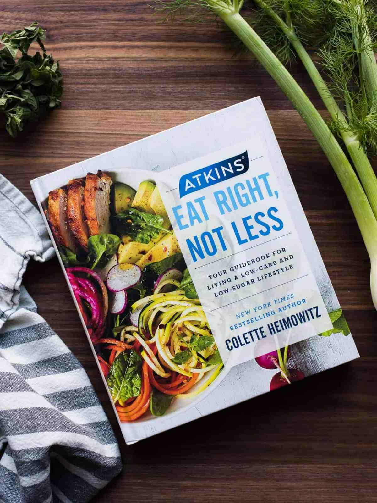 Atkins: Eat Right, Not Less guidebook surrounded by ingredients on a wooden board