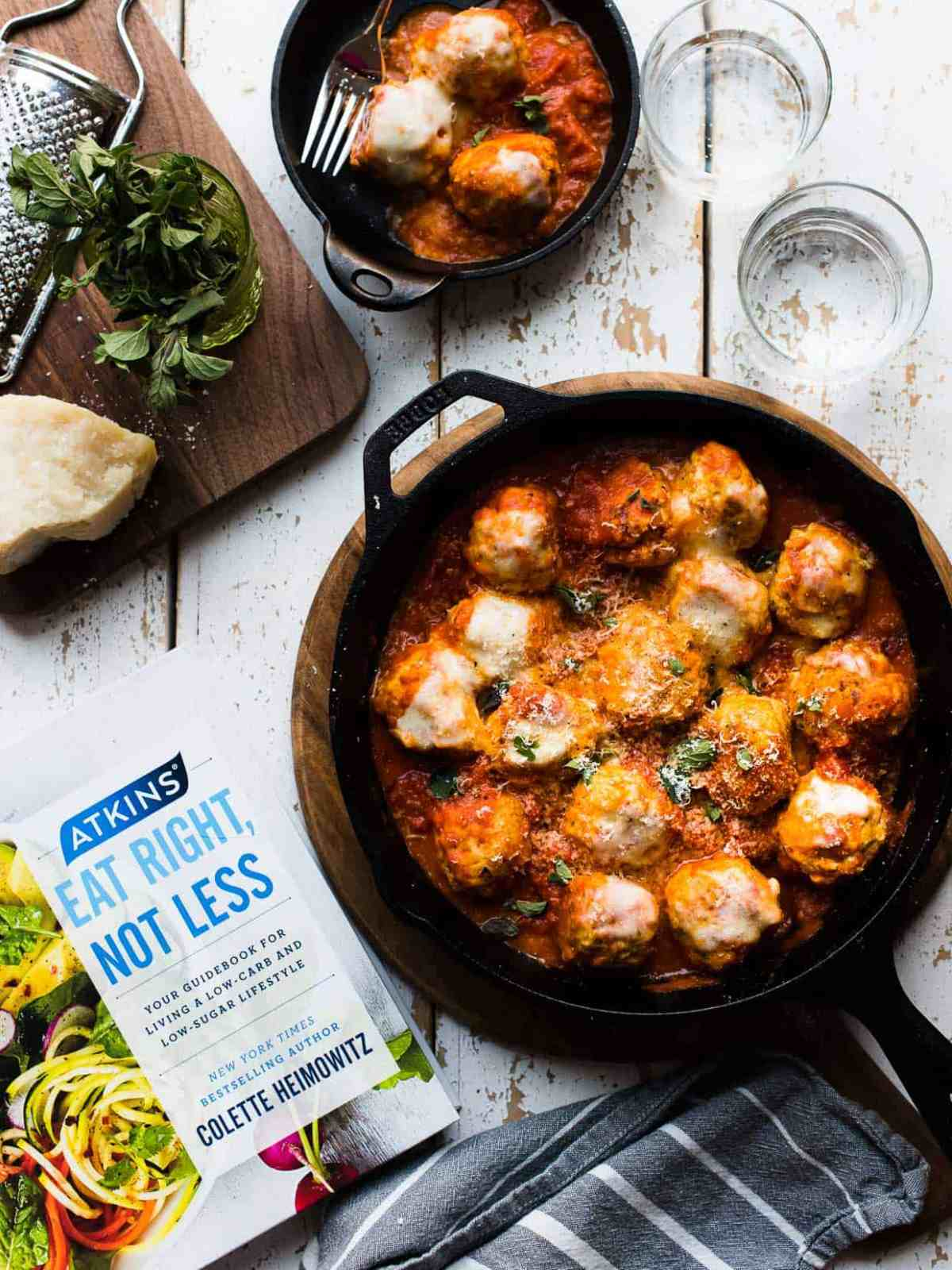 Chicken Parmesan Meatballs in a cast iron skillet next to a copy of Atkins: Eat Right, Not Less guidebook