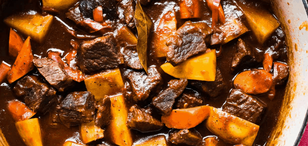 An overhead shot of beef stew in a Le Creuset dutch oven.